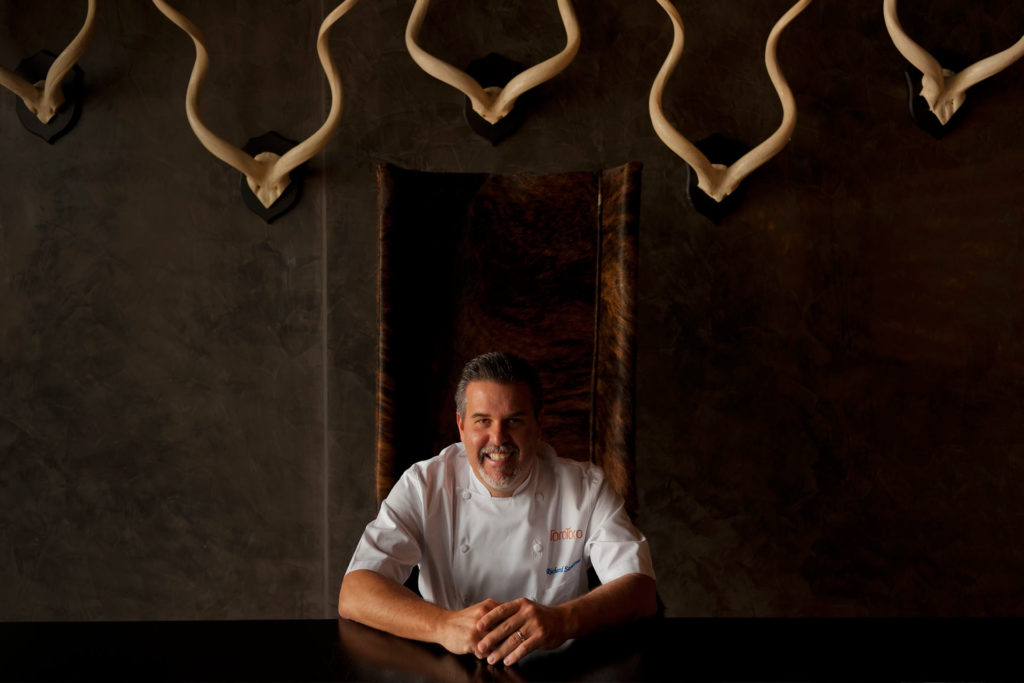 Chef Richard Sandoval smiling white sitting at table