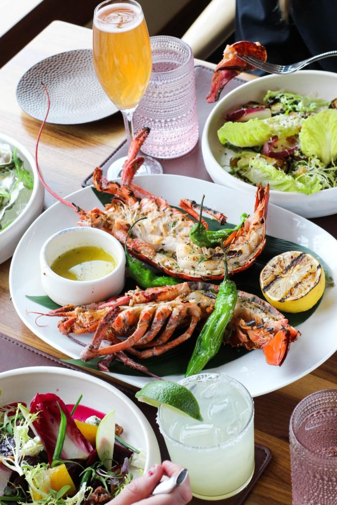 large lobster dish on table of two seated guests ready to eat