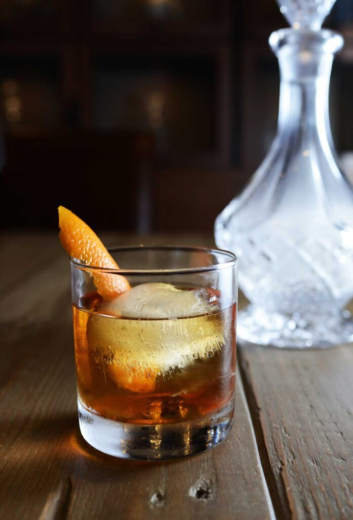 glass of whisky with a slice of orange inside