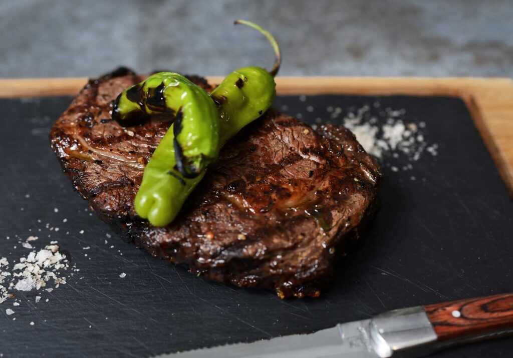 slice of grilled steak topped with two charred green peppers