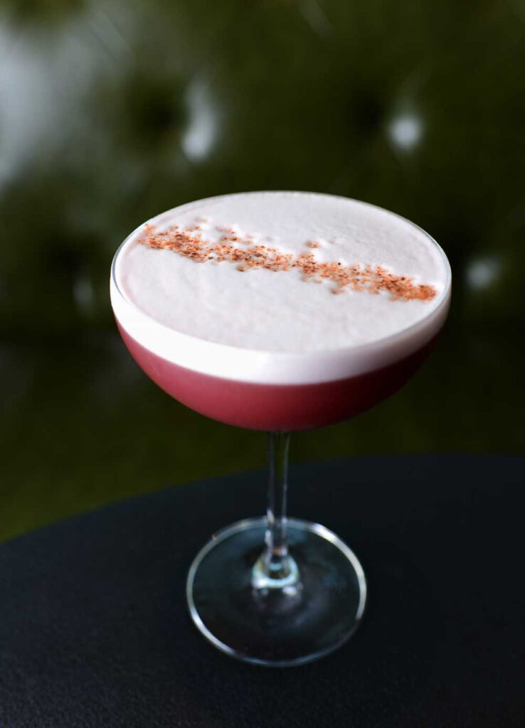 pink cocktail topped with light pink foam and granules of sugar
