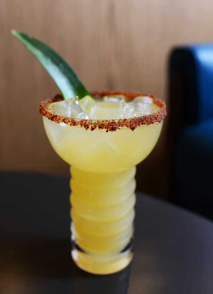 yellow cocktail with a green bean inside and a salted rim