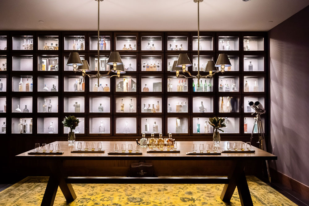 large dining table with chandeliers over it and a large display wall in the back