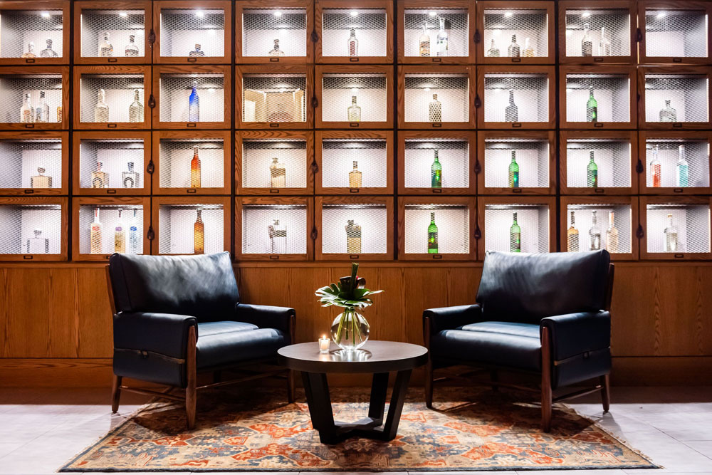 wall covered in display cases of alcohol bottles with two black leather chairs in front of it