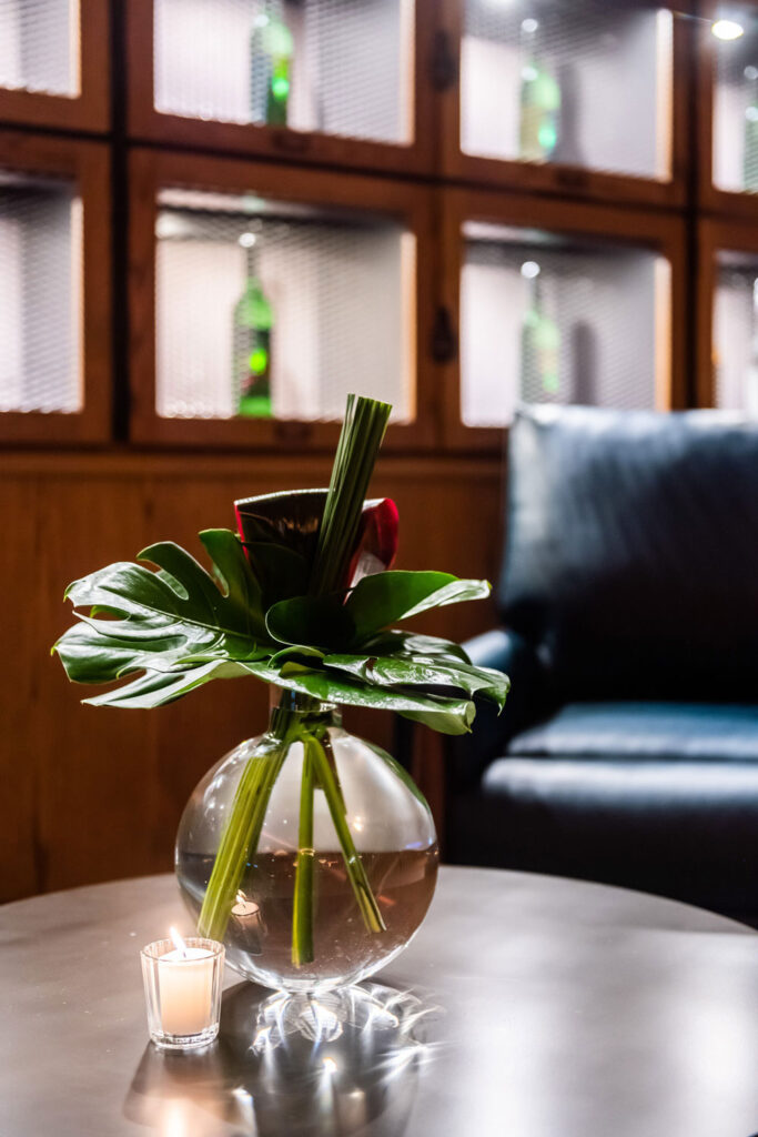 green plant in a clear vase on a wooden table
